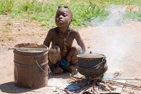 Namibija – deček plemena Himba kuha kosilo